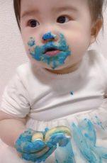 1歳の誕生日お祝いケーキを手づかみで食べる赤ちゃん