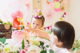 花かんむりをかぶった赤ちゃんと、1歳誕生日ケーキに手を伸ばすお姉ちゃんの姉妹